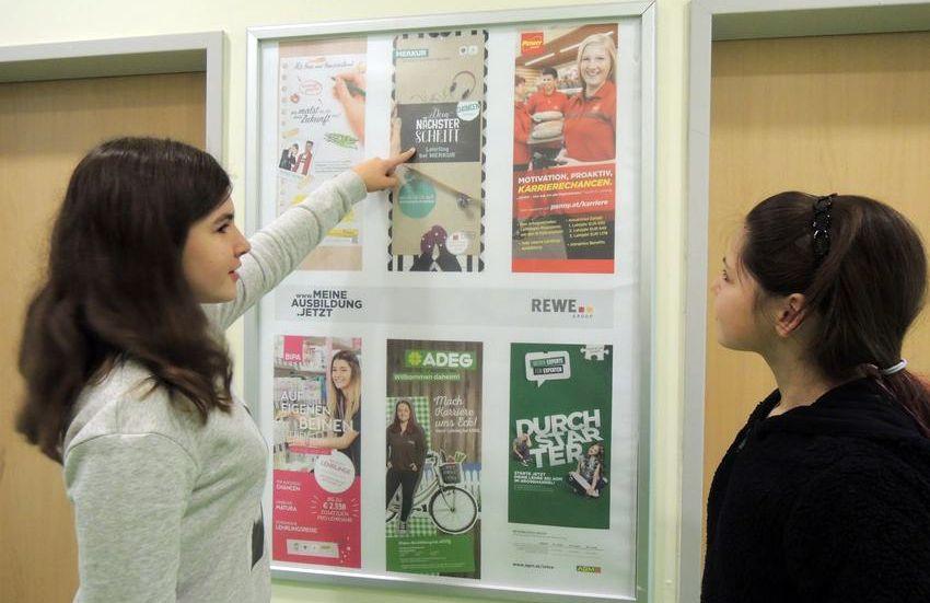Schuelerin zeigt auf Plakat